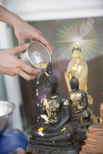 Cropped hand pouring water over buddha statue
