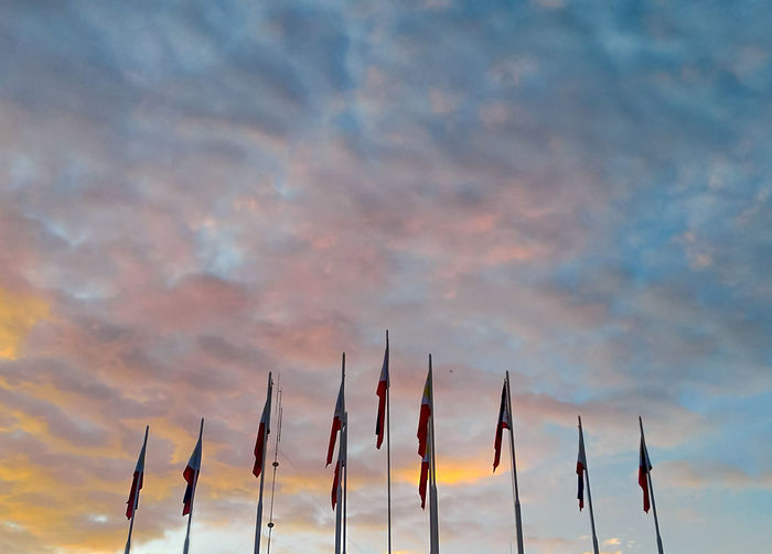 Low angle view of flags against sky at sunset