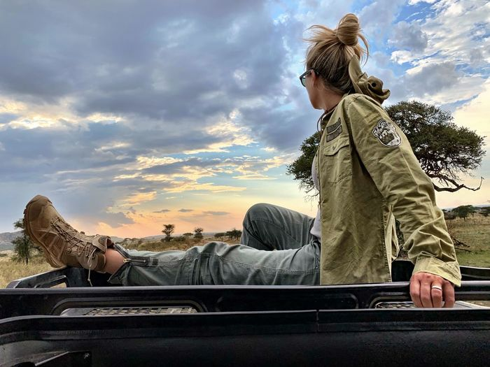Side view of woman sitting on car roof against sky during sunset