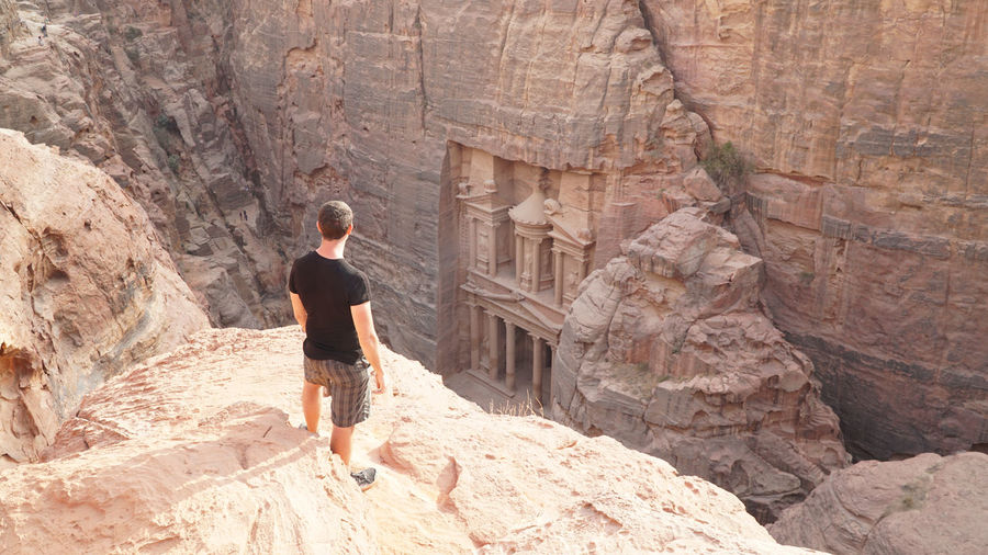 High angle view of man standing on cliff against jabal al-madbah
