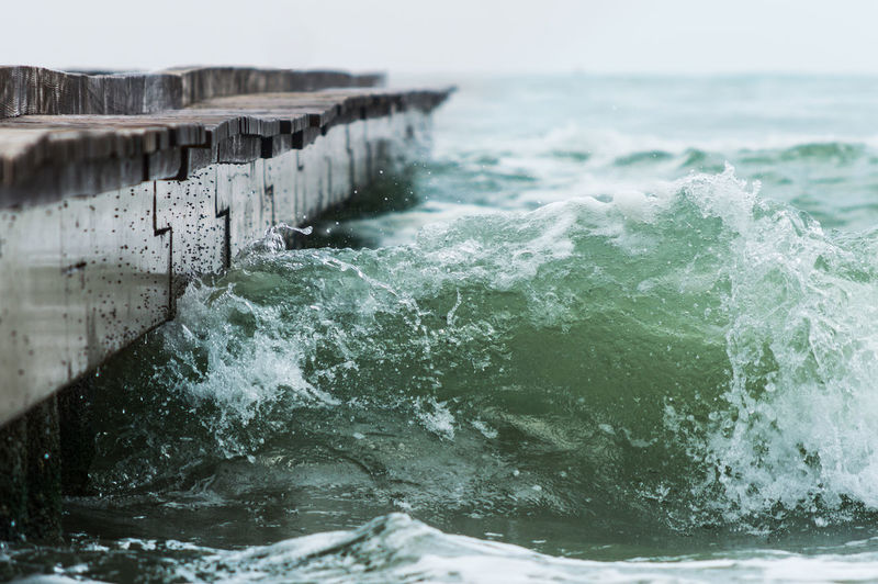 Close-Up Of Waves Breaking Against Pier