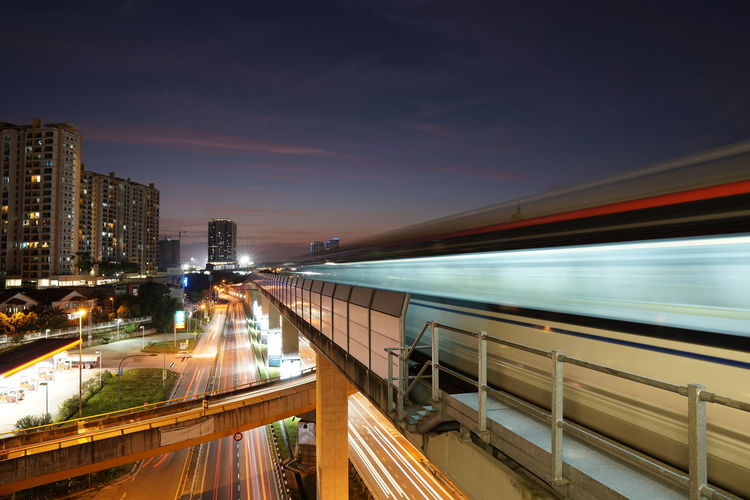 Blurred motion of train in illuminated city at night