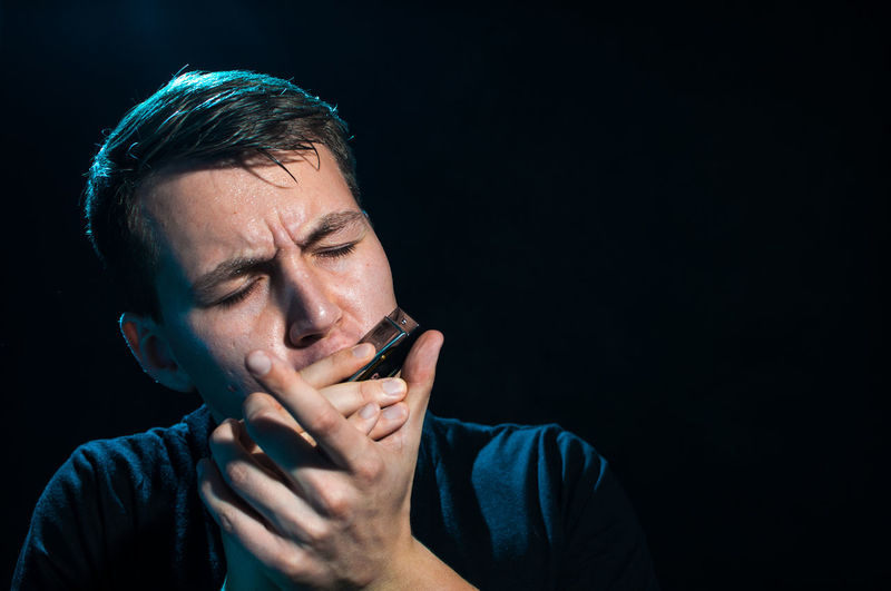 Man playing harmonica against black background