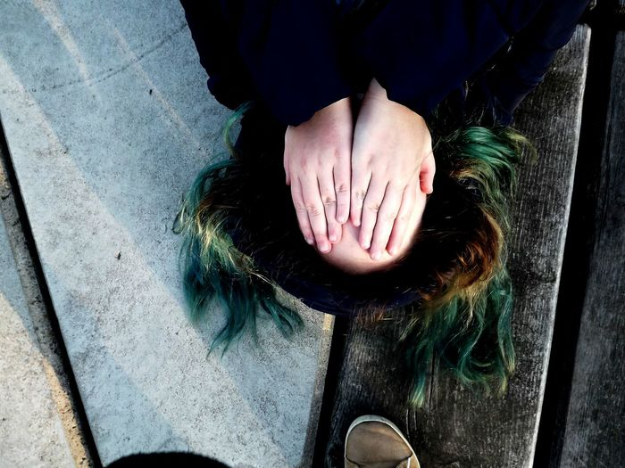 High angle view of woman covering face while lying on wooden floor
