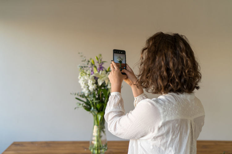 Rear view of woman photographing against wall