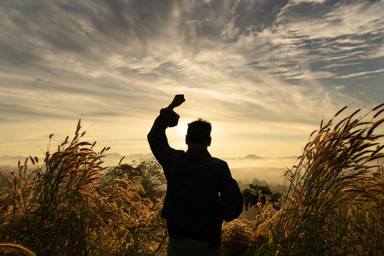 Silhouette man clenching fist on field against sky during sunset
