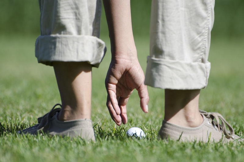 Golfer taking up her golf ball from the grass Adult Ball Close-up Day Golf Golf Ball Golf Course Golfer Grass Green Color Human Body Part Human Hand Human Leg Humor Leisure Activity Low Angle View Low Section Outdoors Pants Part Of Human Body People Picking Up Sport Sunny Women