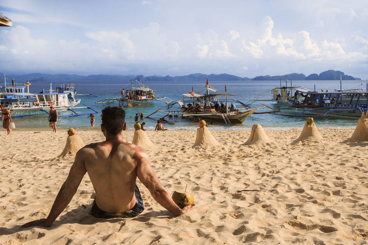 Rear View Of Man Sitting On Beach