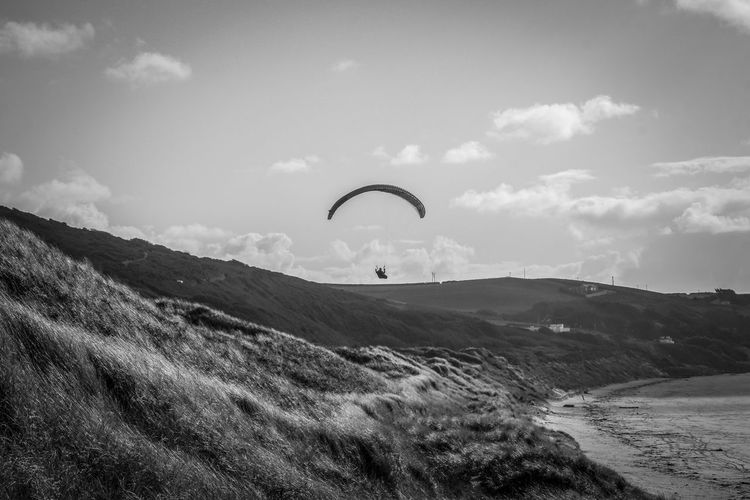 Scenic view of landscape against sky paragliding