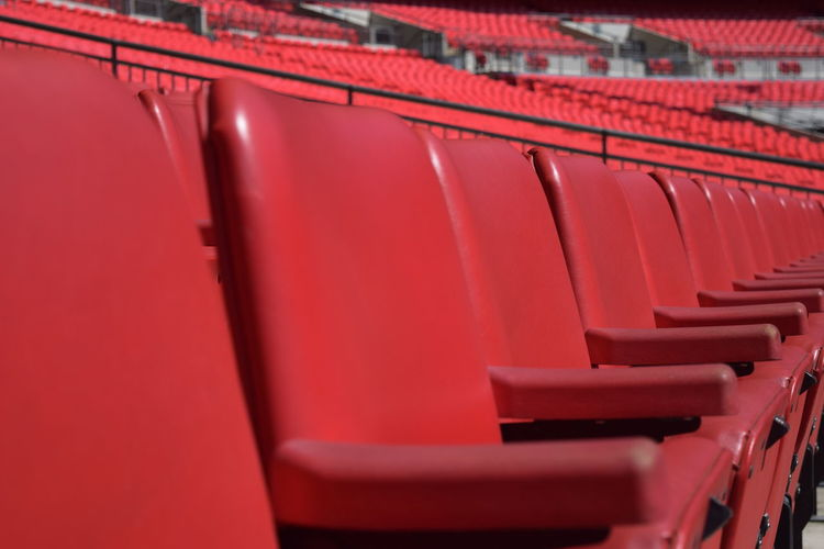 Full frame shot of empty red chairs in stadium