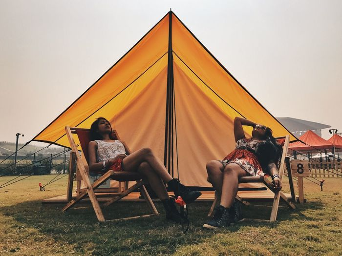Women relaxing on chairs under tent at campsite against clear sky