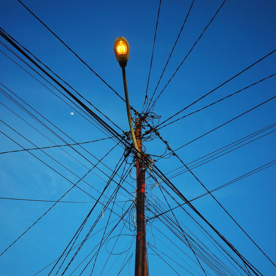 Low angle view of electricity pylon against blue sky