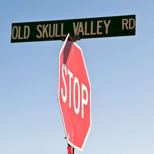 An old road sign in the town of Skull Valley Arizona indicating where old bones dwell. Arizona Skull Valley Blue Capital Letter Clear Sky Communication Day Direction Guidance Information Low Angle View Nature No People Outdoors Red Road Road Sign Rules Sign Sky Stop Sign Text Warning Sign Western Script