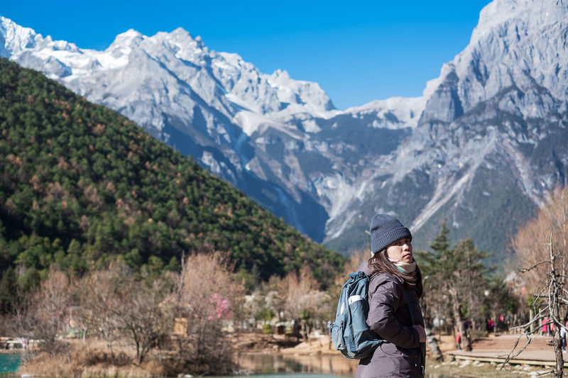 Side view portrait of woman wearing backpack while standing against mountains during winter