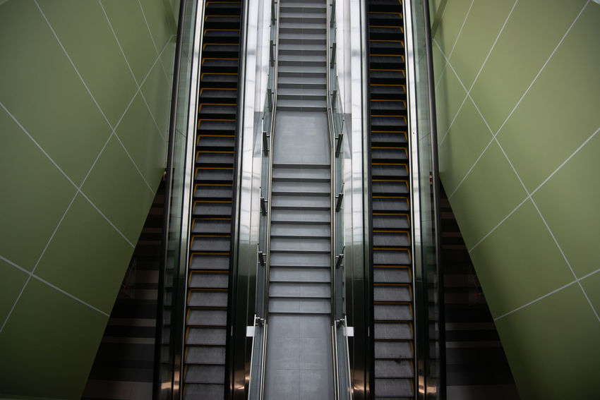 Architectural Column Architecture Building Built Structure Ceiling Day Escalator Illuminated Indoors  Lighting Equipment Low Angle View Modern No People Pattern Railing Staircase Steps And Staircases Wall - Building Feature