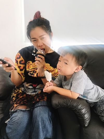 Portrait Of Mother With Son On Sofa Having Ice Cream At Home