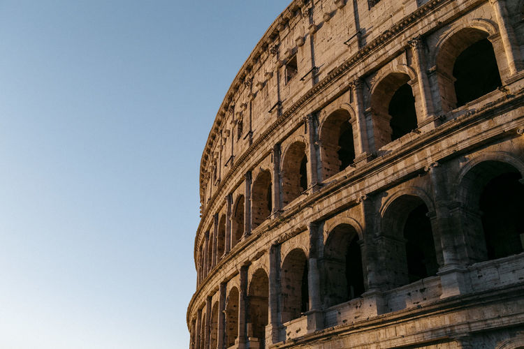 Low angle view of coliseum against clear sky