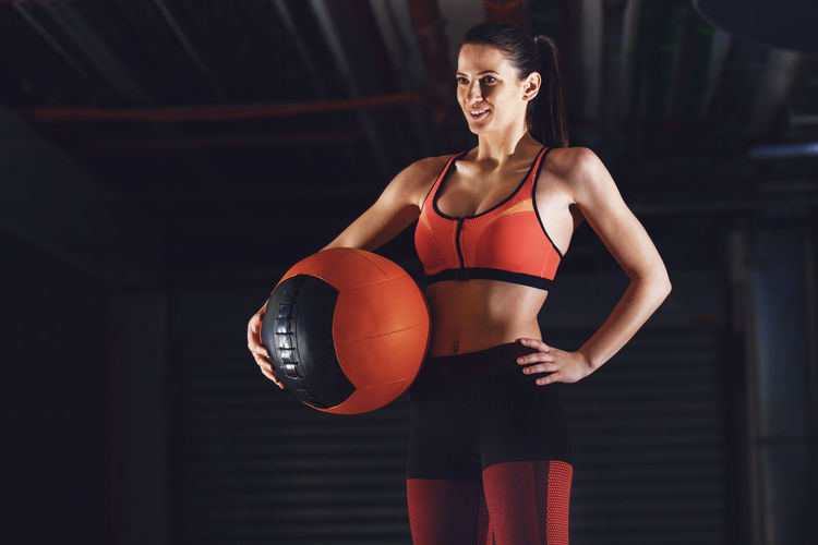 Young Woman With One Hand On Hip And The Other Holding Medicine Ball