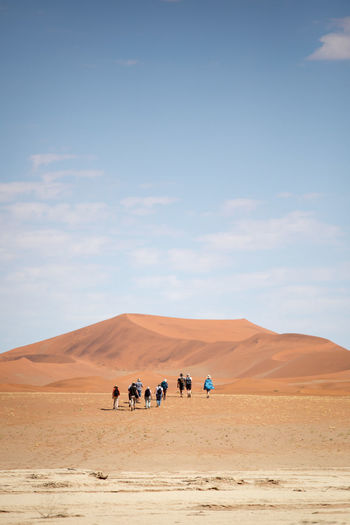 People on desert against sky