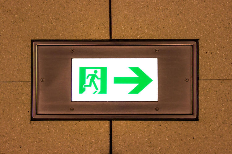 Emergency exit sign on the ground of the airport corridor international. Emergency Flames International Run Security Walk Airport Arrow Symbol Close-up Communication Direction Door Emergency Exit Exit Sign Floor Green Color Ground Information Leaving Move Safety Sign Symbol Warning Sign Way