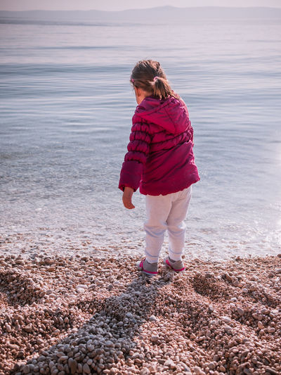 Cute baby girl on pebble beach close to the sea Adorable Beach Calm Casual Clothing Caucasian Child Childhood Children Cute Day Fun Jacket Kid Leisure Lifestyles Little Natural Nature Outdoors Pebbles People Sea Small Water