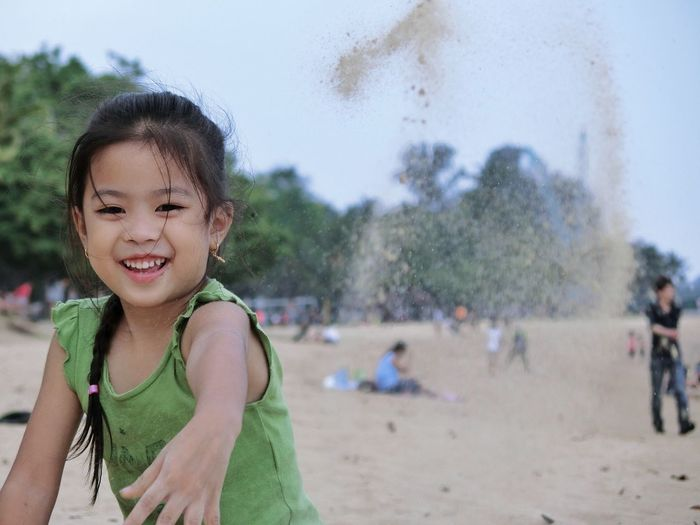 Portrait of cute girl playing with sand at beach
