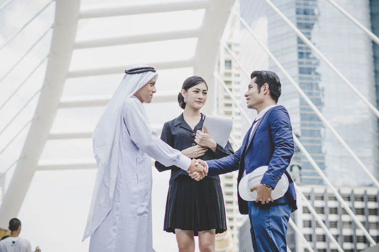 Business people handshaking against metallic structure