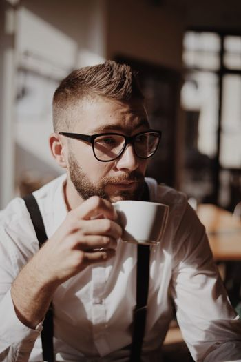 Handsome Young Man Holding Coffee While Sitting In Cafe