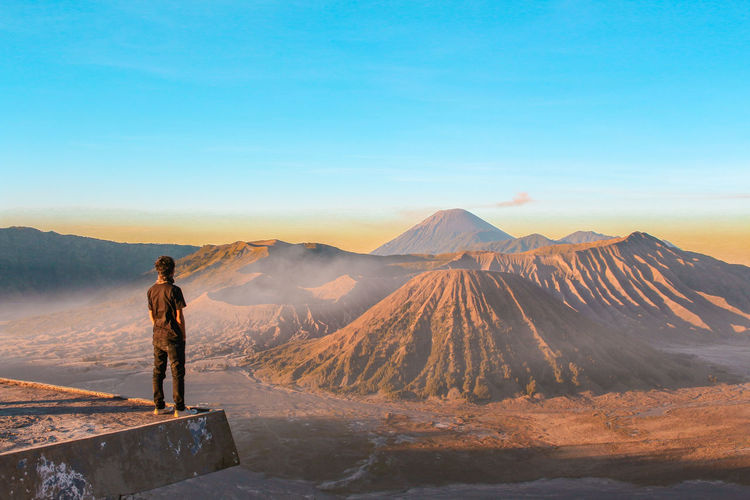 Man Standing At Observation Point Against Mountains During Sunset