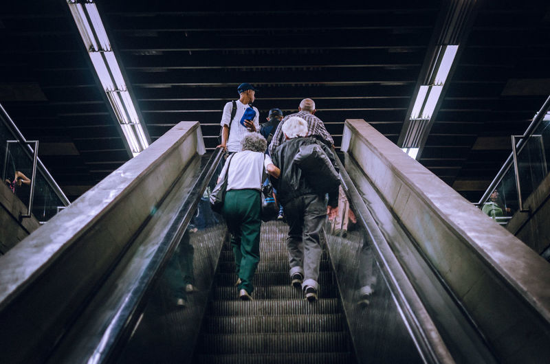 Vamos mi viejo... Capture Tomorrow Low Angle View Escalator Togetherness Casual Clothing Adult People Indoors  Built Structure Lifestyles Rear View Walking Group Of People Railing Men Real People Full Length Steps And Staircases Architecture Staircase Street Photography