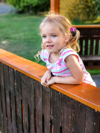 Portrait of smiling girl sitting on wood