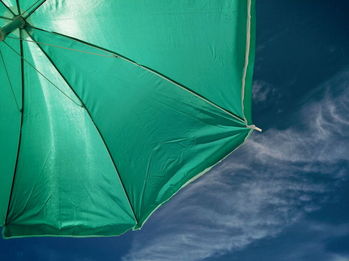 Low angle view of a parasol against the blue sky