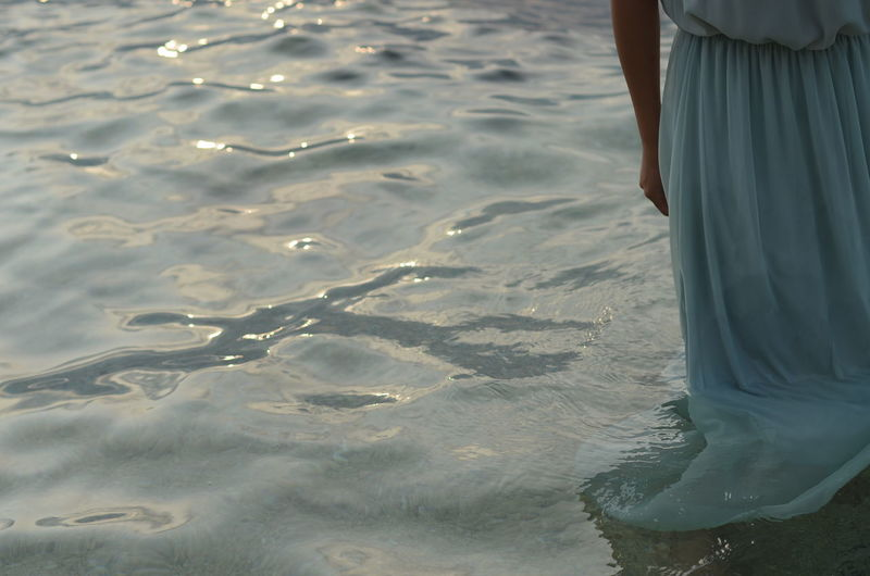 Low section of woman standing in sea