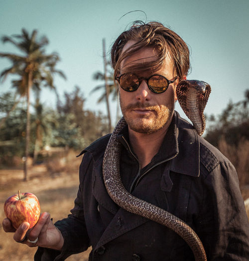 Portrait Of Mature Man With Snake Holding Apple Standing Against Sky