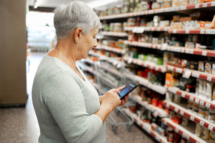 Side view of woman using mobile phone at store