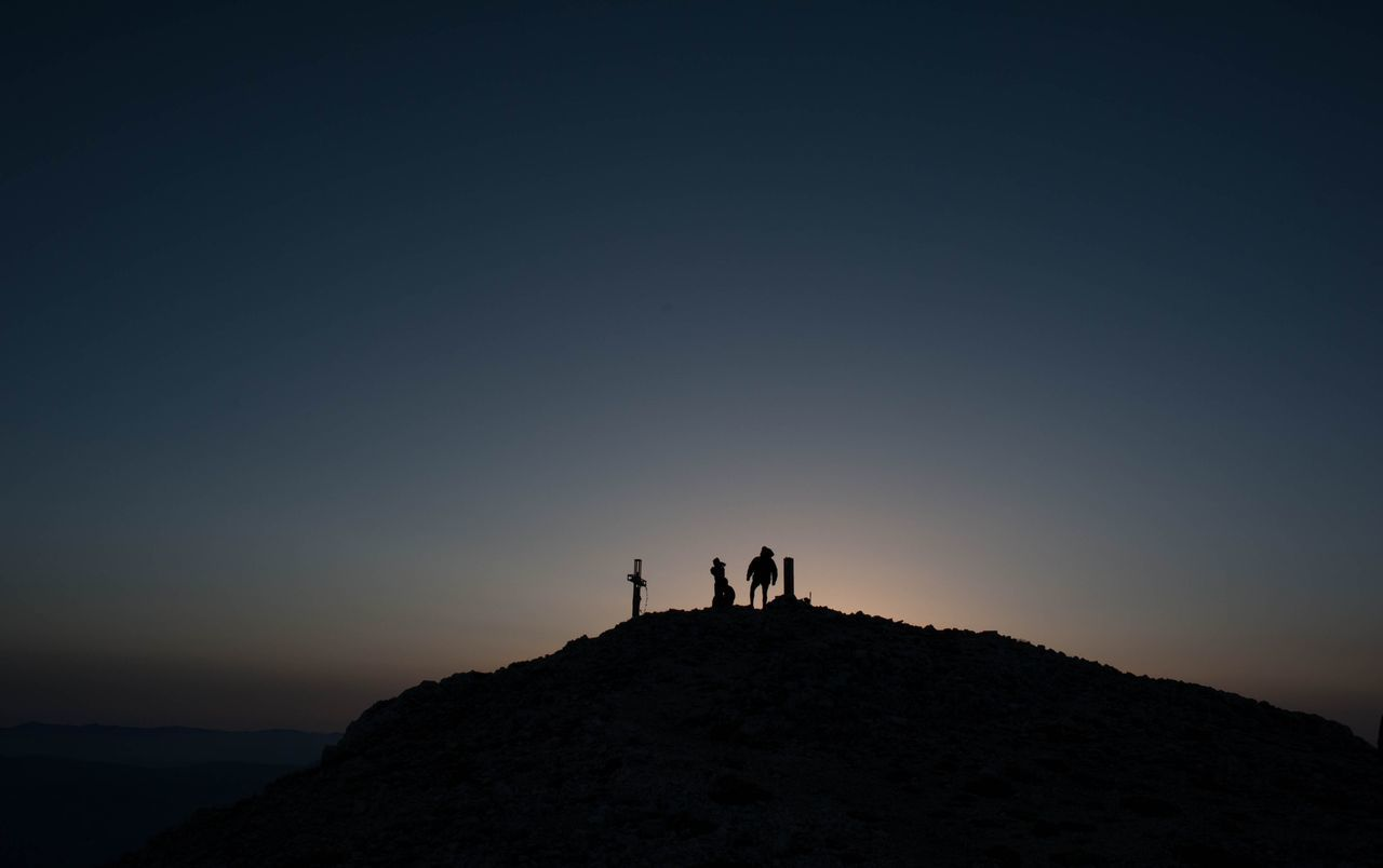 Silhouette people standing on hill against sky during sunset