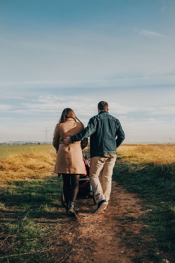 Rear view of couple on field against sky