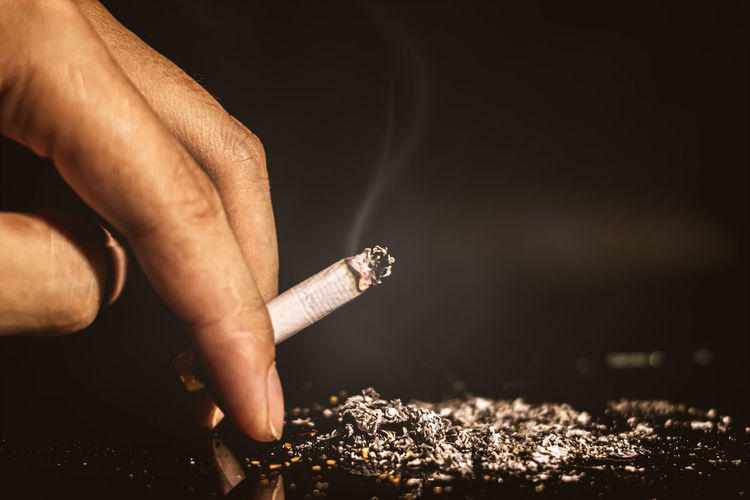 Midsection of person smoking cigarette
