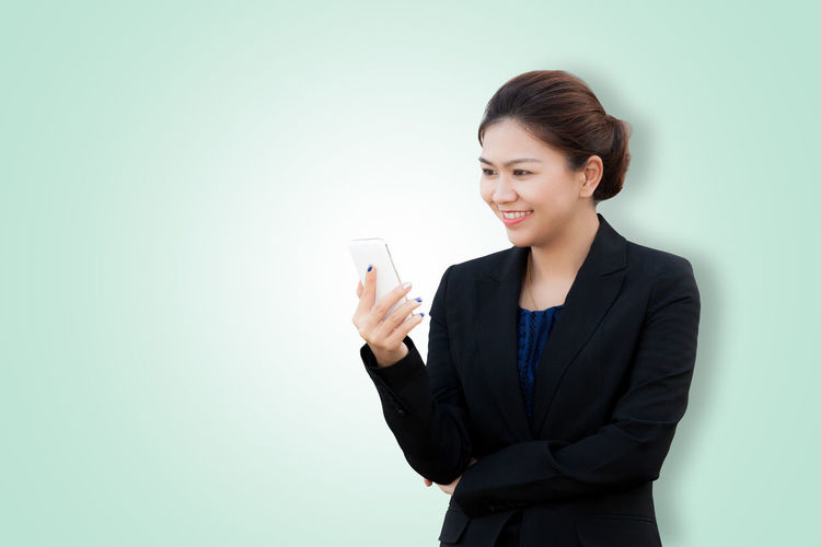 Portrait of smiling business woman looking phone on green background with copy space Asian  Copy Space Isolated Thai Assistant Background Black Business Businesswoman Chat Cheerful Colored Background Communication Happiness Holding Looking Manager Phone Portable Information Device Portrait Secretary Smiling Studio Shot Suit Technology