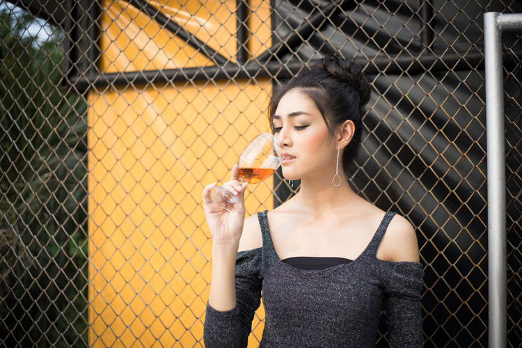 Adult Barrier Beautiful Woman Beauty Boundary Chainlink Fence Drink Drinking Fashion Fence Food And Drink Front View Hairstyle Holding One Person Outdoors Portrait Refreshment Standing Women Young Adult Young Women