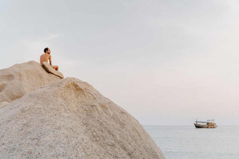 Rear view of naked man sitting on rock