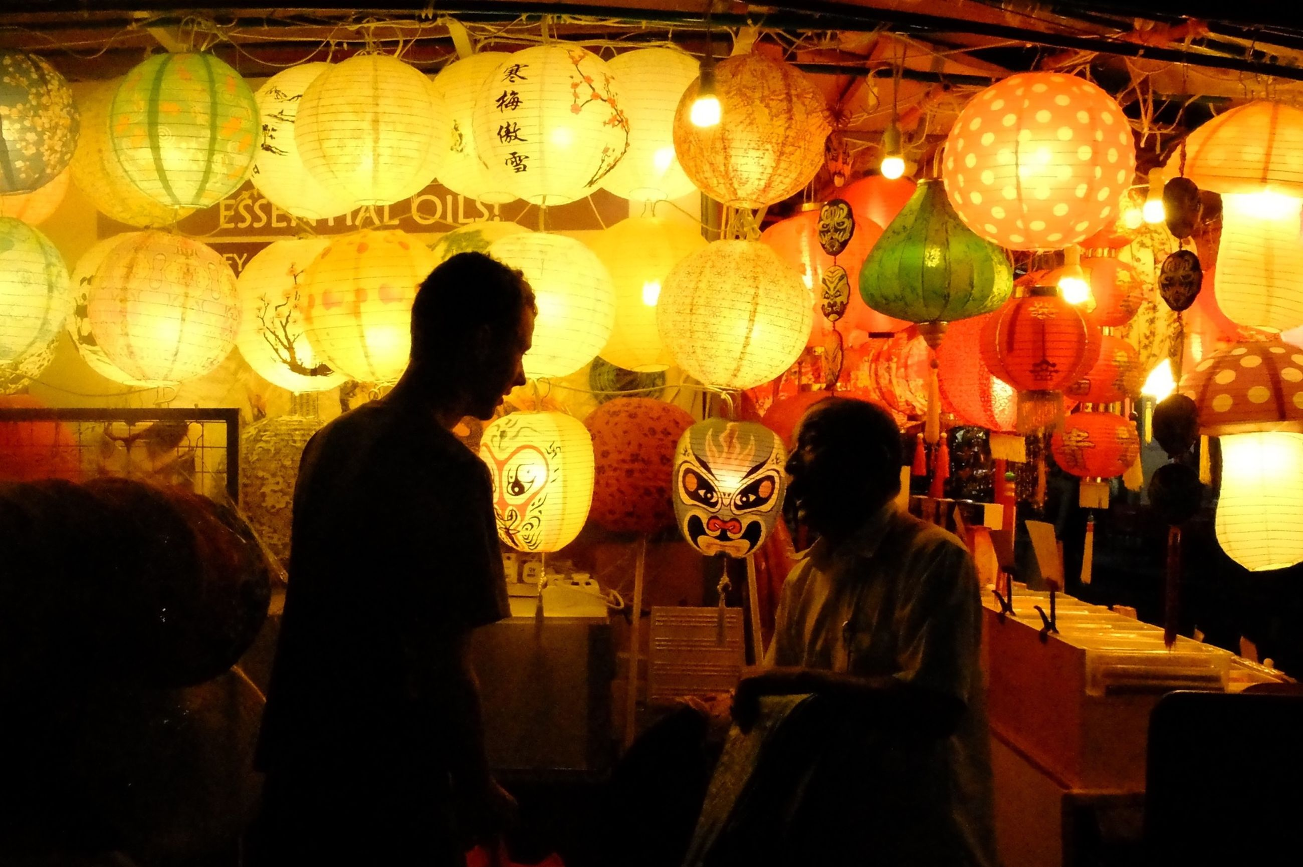 illuminated, indoors, lifestyles, night, men, person, leisure activity, rear view, standing, casual clothing, togetherness, large group of people, lighting equipment, cultures, celebration, lantern, arts culture and entertainment, tradition