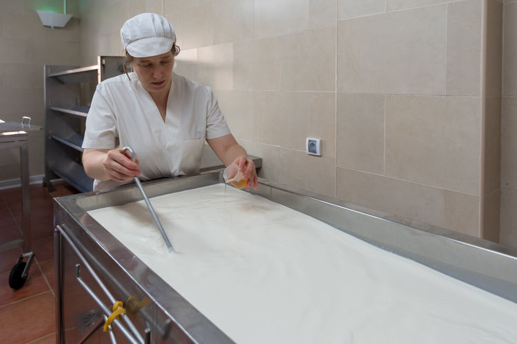 Mature female worker adding liquid to milk while working in cheese factory