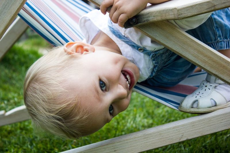 Close-up of boy playing on folding chair