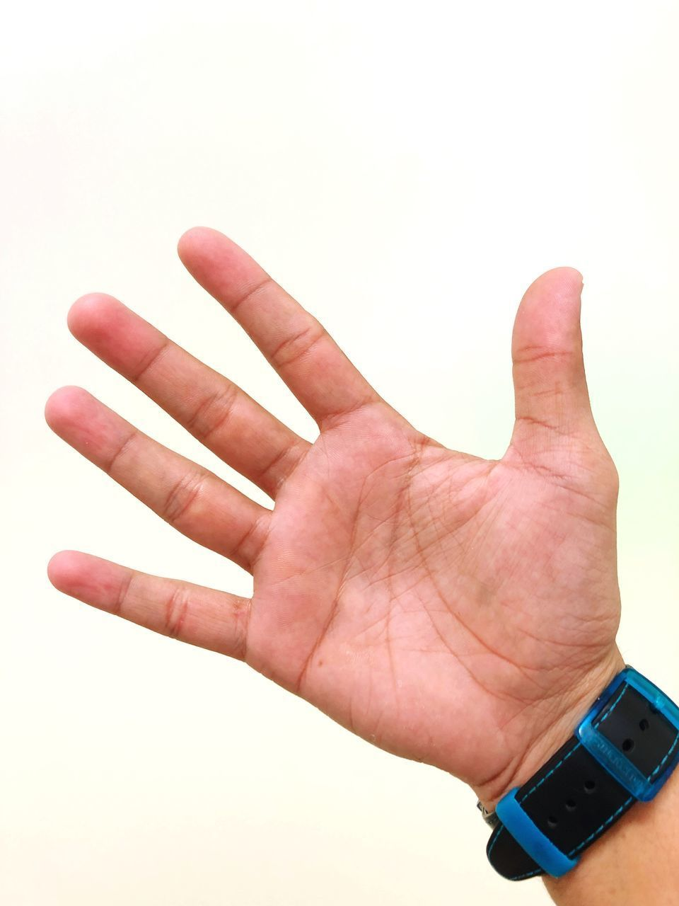 CLOSE-UP OF PERSON HAND AGAINST COLORED BACKGROUND