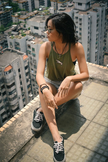 Full length of woman sitting against buildings in city