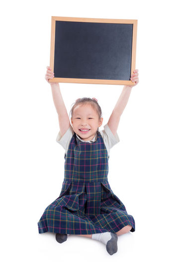 School Girl Board Uniform Asian  Little Background White Isolated Black Holding Smile Happy Young Portrait Cute Happiness Cheerful Child Joy Kid Education Childhood Concept People Beautiful Student Pretty Fun Space Expression Posing Adorable Showing Chalkboard Chinese Korean Thai Sitting Full Length