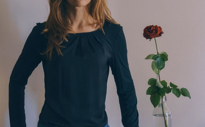 Midsection of young woman standing by rose
