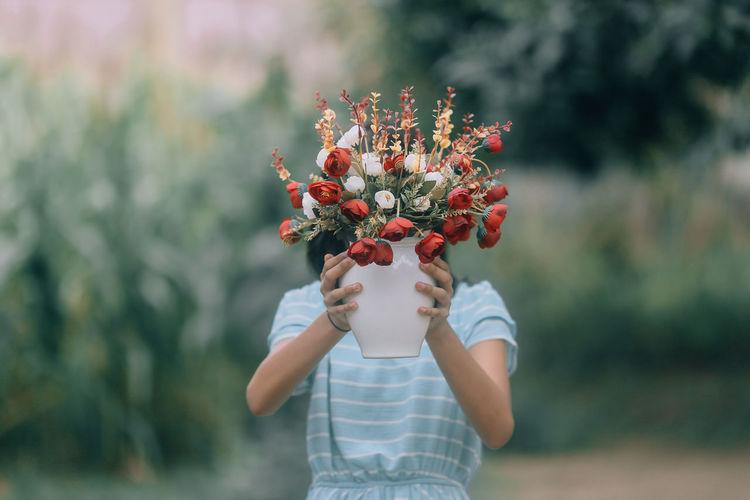 girl holding flowering plant