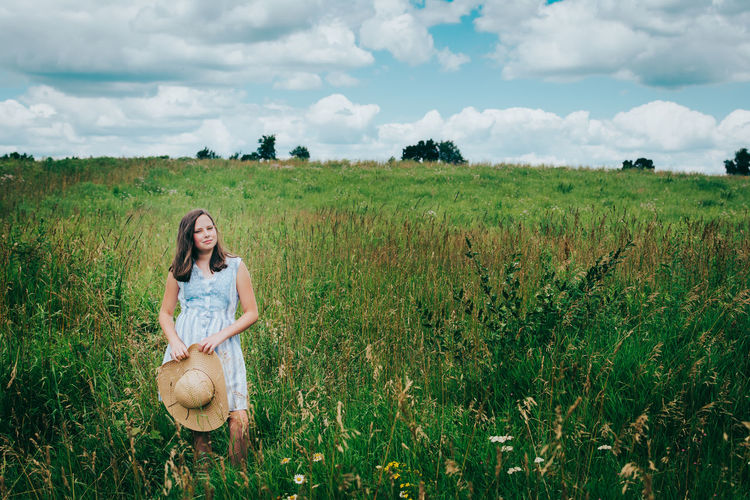 Girl standing in field holding a sun hat